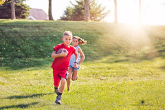 (Rebecca812) Tags: running play football girl boy childhood active healthy twohandtouch outdoors grass sunlight nostalgia sister brother friend playing playful sports americanfootball lensflare portrait candid rebecca812 actionshot canon