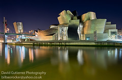 Bilbao Guggenheim at Dawn (david gutierrez [ www.davidgutierrez.co.uk ]) Tags: city longexposure travel bridge blue winter light urban building art water glass colors museum architecture modern reflections photography dawn design gallery purple graphic artistic geometry stones contemporary steel space curves shapes culture gehry exhibition bilbao foundation r guggenheim museo striking titanium 20thcentury frankgehry euskalherria basquecountry solomon masterpiece daring fishscales innovative deconstructivism guggenheimbilbao worldarchitecture davidgutierrez pentaxk5