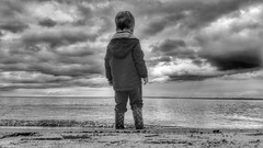 The Tranquillity of Youth (Mark.L.Sutherland) Tags: thetranquillityofyouth youth tranquillity myson boy infant child standing thought sea scotland highlands eastcoast dornochbeach dornoch sand beach sutherland samsung smartphone androidography galaxys5 phoneography cellphone cameraphone blackandwhite bw mono monochrome sky clouds wellingtons wellyboots