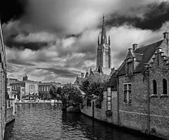 A View of the Church of Our Lady in Bruges  (BW) (Olympus OMD EM5II & mZuiko 12mm f2 Prime) (markdbaynham) Tags: bruges brugge bruggen westflanders flemish historic famous city urban metropolis belgium olympus omd em5 em5ii csc mirrorless evil mft m43 microfourthirds m43rd micro43 micro43rd zd mz zuiko zuikolic mzuiko prime 12mm f2 bw monochrome blackwhite
