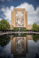 Touchdown Jesus (Fret Spider) Tags: notredame basilica pipes stadium reflection touchdownjesus football campus university alter zeiss loxia2821 sonya7rii mirrorless manuallens southbend indiana duke afternoon september water building library sky cloud symmetry