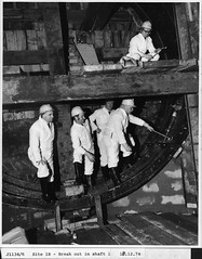 A group of men in a Metro shaft (Tyne & Wear Archives & Museums) Tags: city hardhat urban building men metal shirt architecture standing train hair newcastle underground landscape boot workers construction track industrial shine parts inspection transport group helmet platform tie tunnel cable tools structure retro machinery future gathering nostalgic unusual documentation knee northeast seated crease shafts development futuristic sinking circular mechanics modernist digitalimage interchange excavation tynewear experimentalfilm jesmond futurist industrialheritage civilengineering electrictram blackandwhitephotograph tynewearmetro protectiveclothes publicfunding sandyfordroad warmdigits halfmemory turnersphotographyltd motthayandandersoncollection tynesidemetrolightrailsystem metroshaft forthbankssites consultingcivilengineers haymarketdrives tynepedestriancyclistandvehiculartunnels 18december1974