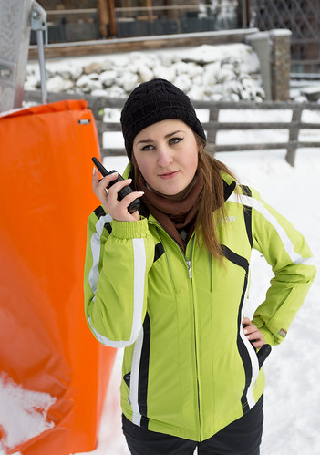 young woman talking on radio at ski slope