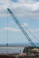 Harbour crane and lighthouse (Mooganic) Tags: uk sea sky lighthouse wales gate harbour crane lock shore buildingsite porthcawl