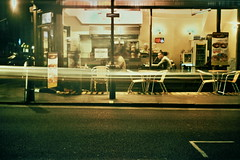 London Nighthawks (The New Motive Power) Tags: city light people urban food london film night analog corner dark evening cafe xpro glow quiet symbol dusk streetlights interior grain lofi slide trail shops late 100 ektachrome sodium smena