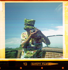 reflected self-portrait with Kodak Instamatic 177X camera and green hat (pho-Tony) Tags: 126 cameraselfportraits kodakinstamatic177x 28mmx28mm instamatic cartridge obsolete 28mm cassette c26 square klick 100xd 24 expired 1990 rollei c41 kodak 177x