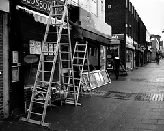 Putting Up New Sign in Byker - Newcastle (Richard James Palmer) Tags: mamiya7ii mamiya 7ii 80mm ilford hp5 ilfordmicrophen microphen ishootfilm shoot film iso 400 iso400 ilfordhp5 f4 newcastle northeast north east street photography streetphotography portrait black white rangefinder medium format 120 filmisnotdead analogue documentary epsonperfectionv700 epson v700 1125 newcastleupontyne upon tyne tyneandwear northern uk england urban melancholy art fineart new overcast isolated walkabout 2016 gritty gloomy abstract trapped blackandwhite monochrome