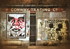 Trading the con way? (maistora) Tags: street door old city uk england urban brown cinema brick london texture abandoned film sign yellow rock metal shop retail wall danger vintage shopping movie grit grey graffiti store gangster ancient graphics rust closed industrial market britain antique decay background grunge gang heavymetal backstreet retro warehouse busy faded earthy lane posters doom backdrop gloom hiphop cinematic whitechapel derelict ghetto stalls aldgate patina squaremile signeage maistora peticoat flickrandroidapp:filter=none