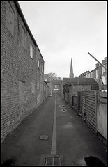 A New Parish (tatrakoda) Tags: old uk england urban bw building history church monochrome 35mm geotagged mono town blackwhite alley nikon lincolnshire steeple spire holy trinity housing analogue tac f5 ilford fp4 grade2 listed backlane artscentre gainsborough terraced tetenal ultrafin tenfoot dn21 britanniaterrace