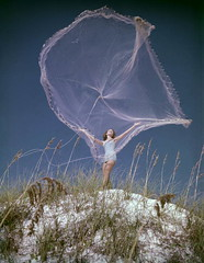 Woman throwing a fishing net high up in the air - Florida