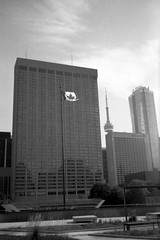 Canadian Flag and Sheraton Centre, Toronto (Richard Wintle) Tags: foma fomapan 200 adonal adox blackandwhite bw monochrome film 135 35mm 38mm f35 canon sureshot sureshotmax toronto ontario canada downtown sheratoncentre flag canadianflag nathanphillipssquare cntower