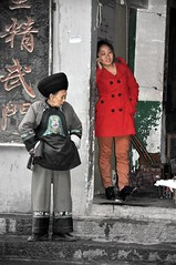 2 Worlds Apart (missgeok) Tags: china travel red colors vertical composition contrast interesting colours candid creative streetphotography streetscene textures difference juxtaposition fenghuang hunan redcoat nationalgeographic youngandold travelphotography cultureclash newandold generationgap 2generations streetcapture selectivecolours modernandold nikond90 2worldsapart girlandoldlady