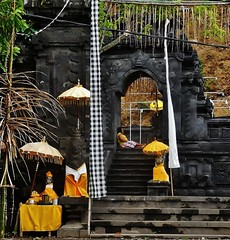 the temple at Candidasa (SM Tham) Tags: asia indonesia bali island candidasa town temple puri gateway steps statues stonecarvings umbrellas parasols ceremonialcloths decorations lady woman archway outdoors architecture