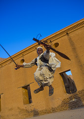 Beja Tribe Man Dancing In Front Of The Khatmiyah Mosque At The Base Of The Taka Mountains, Kassala, Sudan (Eric Lafforgue) Tags: africa travel men vertical architecture outdoors photography dance jumping day northafrica soedan islam sudan religion bluesky dancer mosque tribal sword warrior copyspace tribe oneperson beja soudan placeofworship saharadesert northernafrica traditionalclothing realpeople traveldestinations colorimage lookingatcamera jalabiya fulllenght lowangleview  1people kassala szudn sudo  northernsudan northsudan     bejawi eri9679  xuan