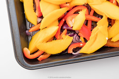 Mix of olive oil, sliced red onion, sliced bell pepper and mango species in black baking pan. Pepper and salt. Step in order to prepare gratin. (annick vanderschelden) Tags: humanhand slice bellpepper redonion pieces gratin cooking baking oven food culinary cuisine preparation slices chopped pointofview mango fruit pepper salt