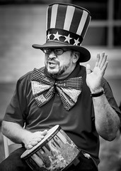 Drummer (melmark44) Tags: props street candid drummer streetphotography blackandwhite man drum stars stripes bowtie hat silly performer kiddies children beard watch 85mm f18 percussion costume primelens canon blur bokeh background photography photographer greyscale grayscale music instrument musicalinstrument singing singer toddlers eyeglasses bethesda maryland smooth