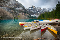 Canoes at Moraine Lake (RichHaig) Tags: moranelakelodge pinetrees canoes dock landscape snow lake water alberta mountains morainelake canada richhaig nikonnikkor1424mm nikond800 clouds banffnationalpark banff