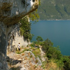 Hiking along the steep mountain edge of Lake Garda (Bn) Tags: blue summer vacation sky italy mountain lake holiday alps colour green nature water sport del clouds forest trekking river walking landscape fun lago coast canal waterfall carved topf50 san garda rocks stream paradise mediterranean italia sailing terrace hiking path air deep rocky tunnel panoramic via mount explore trail step alpine valley ravine gorge michele fjord pastures climber shape overlooking majestic bushes shrubs climate gardameer bassa campione brasa baldo 50faves 4hr nr266 nr267 prapione 2218m afvanture