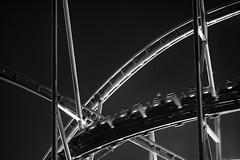 Coaster ({Luminous Flux}) Tags: coaster rollercoaster black white monochrome movement speed rigid metal steel construction lines dark night lights sky rails wagon fast people fun gradient curves