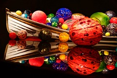 Chihuly glass in a boat (johnsinclair8888) Tags: glass reflection chihuly boat colors art nikon tamron tamron2470 d750 seattle red blue green museum light rowboat stage theater display vibrant balls