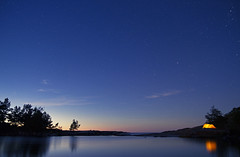Camping by the sea (Muppian) Tags: sea sky night stars tent camping water trees reflection light