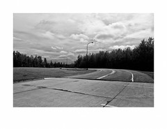 Rest Area along Highway 53, near Half Moon Lake (Richard C. Johnson: AKA fishwrapcomix) Tags: leicaq summilux28mm f17 digital paxamericanus endofempire civisromanussum thegreatrecession ironrange minnesota midwest outdoor landscape restarea blackandwhite bw monochrome sunsetsinthewest sunrisesintheeast wetzlar reddot tarmac pinetrees lights clouds