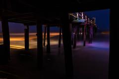 colors under the pier... (AnnPorter) Tags: ocean light orange sun black beach dark fun photography pier sand slow purple dunes under grain calm shutter ann outer grainy porter banks obx annporter