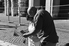 Delicately Tender (Smith-Bob) Tags: out outside outdoors street people candid man men dude dudes woman women wife sister friend husband brother family lost map search tourists rome roma colosseum history historic icon iconic bloody touristattraction bw blacknwhite blackwhite shootingfromthehip hip fromthehip italy italia europe