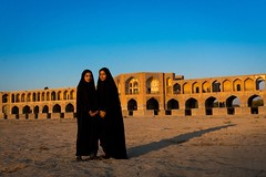 Portrait of two young women in chadors in front of Khaju bridge Pol-e Khaju, Esfahan in Iran. (Eric Lafforgue) Tags: 2people ancient arches architectural architecture attraction blue bricks bridge chador clearsky colorimage copyspace day dried esfahan fullframe fulllength hispahan horizontal iran iran20161210 iranian isfahan ispahan khajubridge lookingatcamera middleeast muslim orient outdoors persia photography river spadana sunny tourism touristic traveldestinations twopeople unescoworldheritagesite urban veiled women womenonly youngadults zayandeh