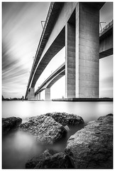 Gateway Bridge (JakaPH Photography) Tags: filter nd city cityscape brisbane bridge day daylight clouds long exposure river water rocks big huge queensland australia black white bw lee little stopper movement majestic sky landscape leading lines