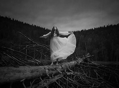 The Balancing Act (Maren Klemp) Tags: fineartphotography fineartphotographer darkart darkartphotography blackandwhite monochrome balancing woman tree nature outdoors painterly texture movement whitedress windy ethereal selfportrait portrait forrest lake water vintage conceptual surreal