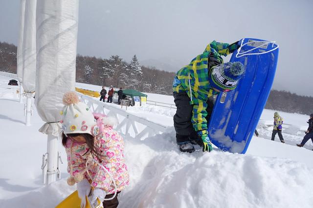 雪の滑り台を滑走する準備をする子供達。|キープファームショップ
