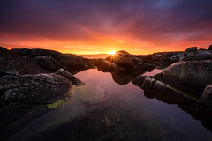 Final Light (Arvid Bjrkqvist) Tags: kungsbacka valldasand light sun sweden rocks reflections water ocean sea coast sunset sky clouds fiery rays evening mood dark blue red purple orange yellow