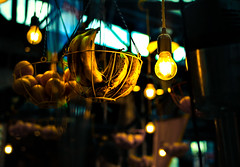 Lighting (rlerner25) Tags: light lighting lightbulb market colors fruit bannan banana mango stand hanging bulb high aperture wire indoor windows window basket metal glass