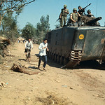 02 February 1968, Da Nang, South Vietnam --- Refugees Fleeing Alongside Armored Vehicle on Dirt Road thumbnail