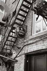 A sign of Guinness goodness located therein (Mike Wood Photography) Tags: streetphotography street fireescape stairs signs sign guinness beer wall lookingup blackandwhite blackwhite arr allrightsreserved mikewoodphotography