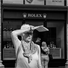 Watch (John Riper) Tags: johnriper street photography straatfotografie square vierkant bw black white zwartwit mono monochrome hungary budapest candid john riper fujifilm fuji xt1 18135 woman lady watching rolex window sun map guide crown tourist
