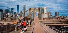 2016 - New York City - Brooklyn Bridge - Tower - 3 of 5 (Ted's photos - For Me & You) Tags: 2016 cropped nikon nikond750 nikonfx nyc newyorkcity tedmcgrath tedsphotos vignetting pedestrians walking walkers people peopleandpaths railing towers cables oneworldtradecenternyc backpack shadows verizon shorts usaflag flag walkway vehicle highrise manhattan bridge