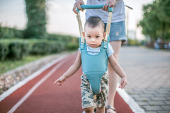 Mother teaching baby boy how to walk (HIKARU Pan) Tags: 1dx 50l asia canonef50mmf12lusm china eos1dx photography portrait shanghai babyboy cute family horizontal lovely motherandson outdoors walking youngwoman