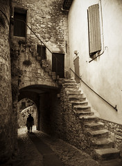 Leaving 2 (CTfoto2013) Tags: silhouettes personnages people alley passage arch ruelle paca france rue medievaltown viellleville oldtown villagemedieval monochrome micro43 mirrorlesscamera lumix gx7 panasonic ambiance mood architecture door porte lumiere light shadows ombre vaisonlaromaine vaucluse paves cobblestones atmosphere mystere mystery provence arche gate calle callejon voute sepia vintage retro stairs escaliers