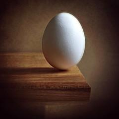 Egg on the edge. (Through Serena's Lens) Tags: mm macromondays edge macro wood board texture stilllife indoor shadow light stationary