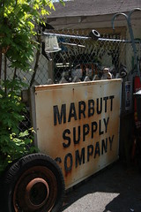 Marbutt Supply Company Sign (Samantha Evans of Samantha Evans Photography) Tags: light shadow red brown sunlight white signs black tree green wheel sign metal rural canon fence silver word rust shadows open letters tire rubber ephemera asphalt countrystore summerville rustysign sooc tamron1750 canon60d summervillega marbuttsupplycompany