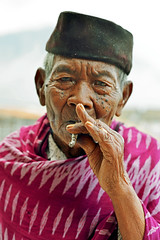 Old smoking man, Java Island (Indonesia) ([cation]) Tags: voyage old travel viaje portrait hat indonesia 50mm java nikon southeastasia hand retrato cigarette smoke smoking chapeau wise sombrero wisdom mirada viejo bromo vieux regard cigarillo d800 fume cation sagesse indonsie traditionnel traditionnal asiedusudest