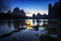 Cormorant Fisherman at Night (Aaron_Choi) Tags: china landscape travel tourism chinese liriver river cormorant fisherman fishing oldman man bird beautiful magnificient xingping yangshuo asia asian riverbank sunset bluehours night boat bambooboat bamboo raft lantern light karst mountains mountain hills limestone nature