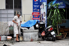 Precious load (Roving I) Tags: cafes street dishwashers workers carrying bowls pile loads caution motorbikes signs cocacola pepsi fragile danang vietnam