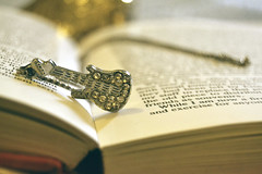 Reading is like a music to me (Ayeshadows) Tags: guitar diamonties chain silver book words music instrument trinket indoor gold bokeh pendant necklace reading habbit goodbook