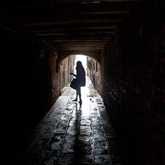Venice - Alleys (Gary Kinsman) Tags: venice italy woman rain silhouette dark bag alley waiting italia alone candid empty streetphotography streetlife tunnel raining venezia 2012 canon28mmf18 canoneos5dmarkii canon5dmkii
