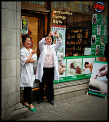 The Acupuncturists (Sven Loach) Tags: camera uk portrait england london sign mobile shop canon workers women lab open herbs britain chinese streetphotography squareformat massage 5d coats acupuncture onlooking thestrand phones shopfront markii londoners
