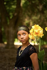 Beautiful girl and flower. (tarheelz11) Tags: girl beautifulyounglady skintone hair yellowflower bokeh blurredbackground portrait pose expression thoseeyes thatlook concentration eyes park raleighnc shelleylakepark dress gold hairband necklace canonef50mmf18ii niftyfifty canoneos7dmkii