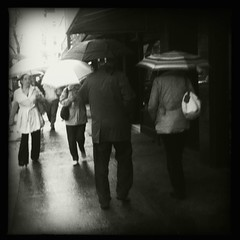 """""""shields from the rain. I don't need a shield. I have the rain inside of me. Pouring down, never ending."""" SK~ (Manhattan Girl) Tags: nyc bw blur rain dark manhattan gritty grainy umbrellas hipstamatic"""